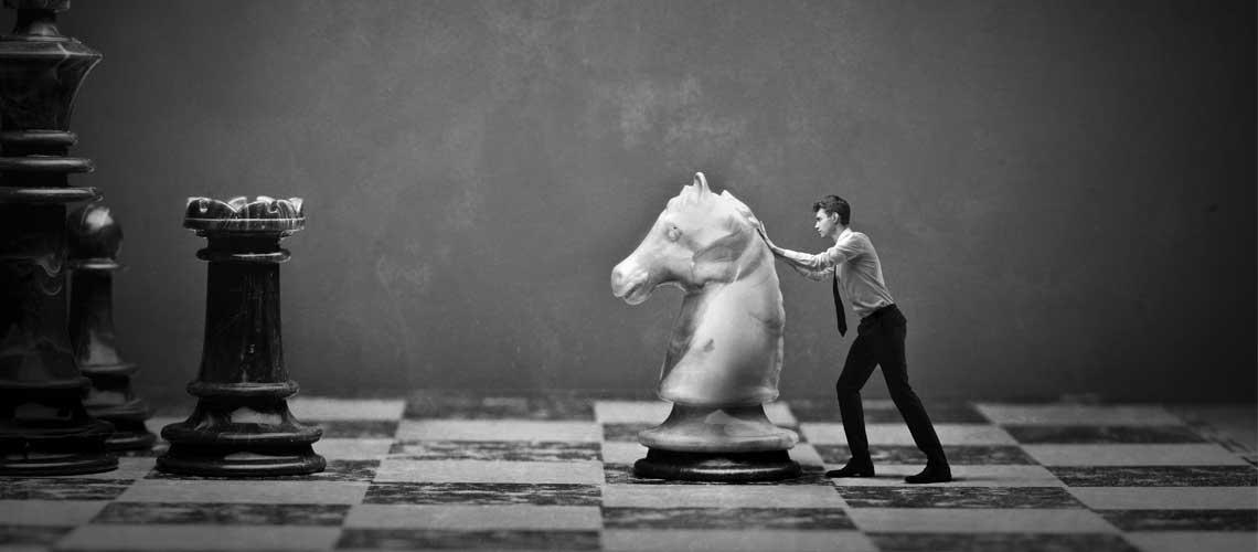 גבר דוחף כלי שחמט על לוח שחמט ענק
